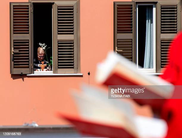A resident reacts as she watches from her appartment Palm Sunday mass celebrated on the rooftop of the San Gabriele dell'Addolorata church in Rome on...