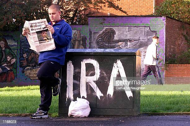 A resident reads a local newspaper October 24 2001 in Andersontown in West Belfast Northern Ireland General John de Chastelain head of the...
