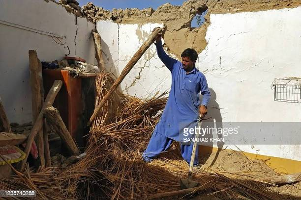 Resident removes debris of his mud house that collapsed following an earthquake in the remote mountainous district of Harnai on October 7 as around...