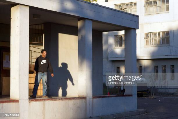 A resident Ricky Asher poses at the formerly deserted Helen Bowden Nurses home where he lives with his family illegally but without electricity and...