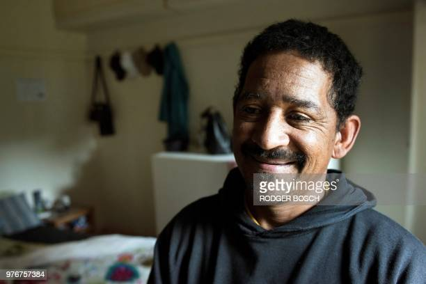 A resident Ricky Asher stands in his room at the formerly deserted Helen Bowden Nurses home where he lives with his family illegally but without...