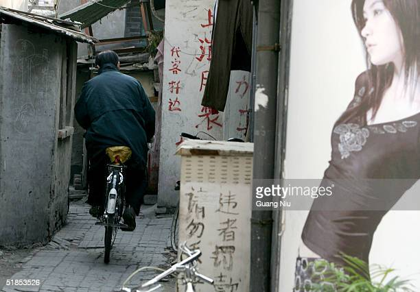 A resident rides a bicycle into a hutong or alley on December 13 2004 in Beijing China Hutong is an ancient city alleyway or lane typical of ancient...
