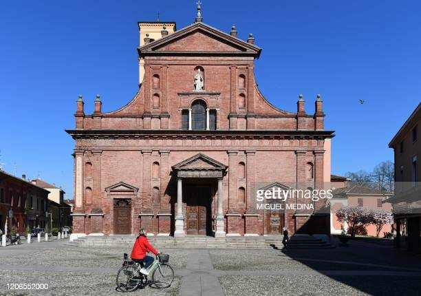 A resident rides a bicycle past the San Biagio and Santa Maria church in central Codogno southeast of Milan on March 11 2020 a day after Italy...