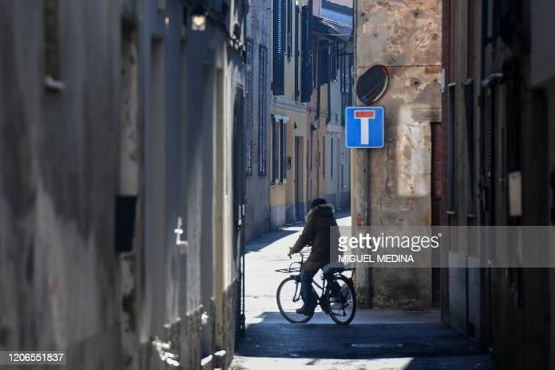 A resident rides a bicycle through a deserted street in Codogno southeast of Milan on March 11 2020 a day after Italy imposed unprecedented national...