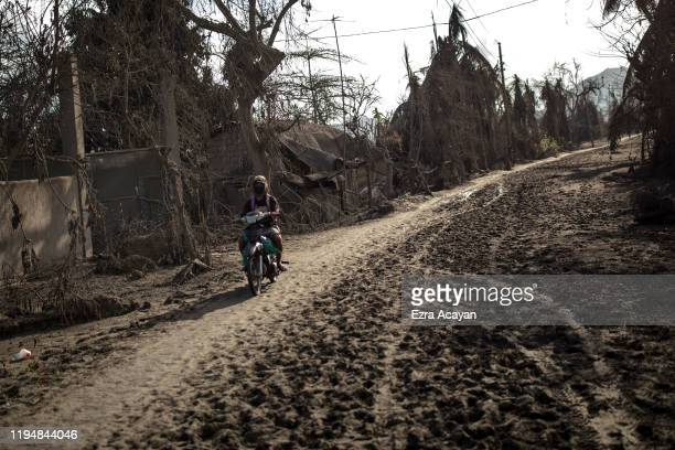 A resident rides a motorbike along a highway covered in volcanic ash from Taal Volcano's eruption on January 20 2020 in the village of Buso Buso...