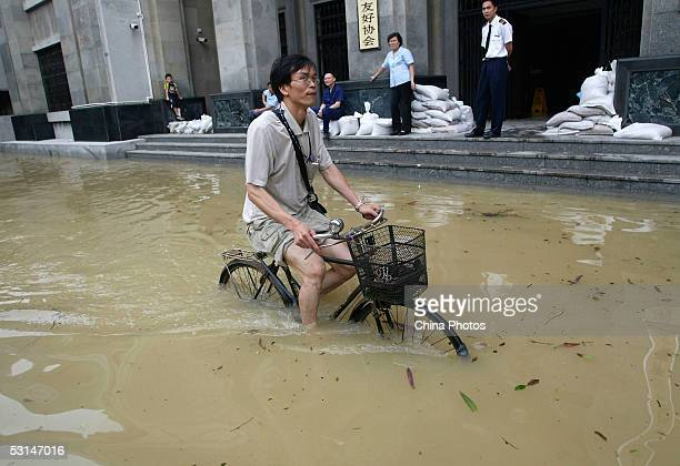 Resident rides his bicycle through flood waters on June 24, 2005 in Guangzhou, Guangdong Province, southern China. President Hu Jintao has ordered...
