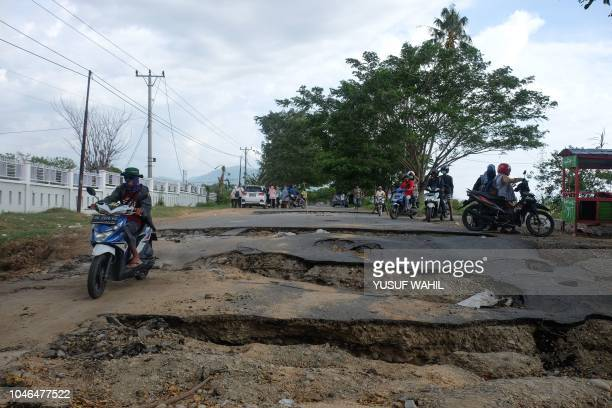 A resident rides his motorcycle on a damaged road in Sigi Indonesia's Central Sulawesi on October 6 following the September 28 earthquake and tsunami...