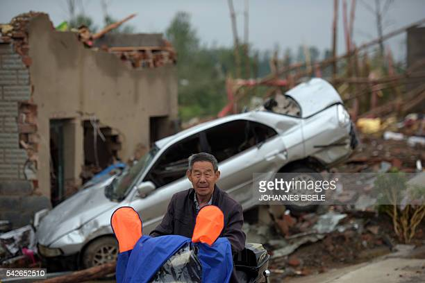 A resident rides past rubble of destroyed houses after a tornado in Funing in Yancheng in China's Jiangsu province on June 24 2016 Extreme weather...