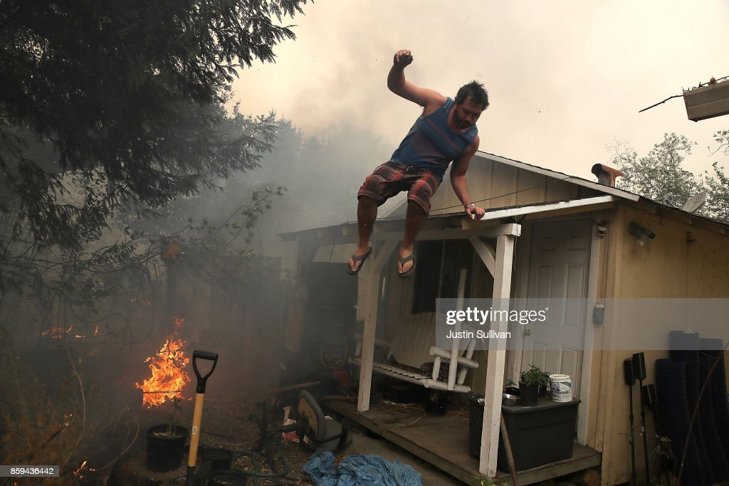 A resident rushes to save his home as an out of control wildfire moves through the area on October 9, 2017 in Glen Ellen, California. Tens of thousands of acres and dozens of homes and businesses have burned in widespread wildfires that are burning in Napa and Sonoma counties.
