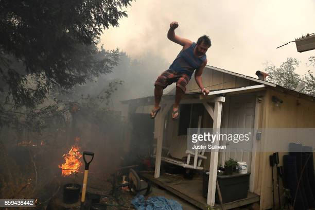 A resident rushes to save his home as an out of control wildfire moves through the area on October 9 2017 in Glen Ellen California Tens of thousands...