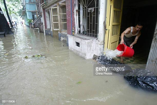 A resident scoops water from his flooded house at Shamian Island on June 22 2005 in Guangzhou of Guangdong Province southern China Streets in Shamian...