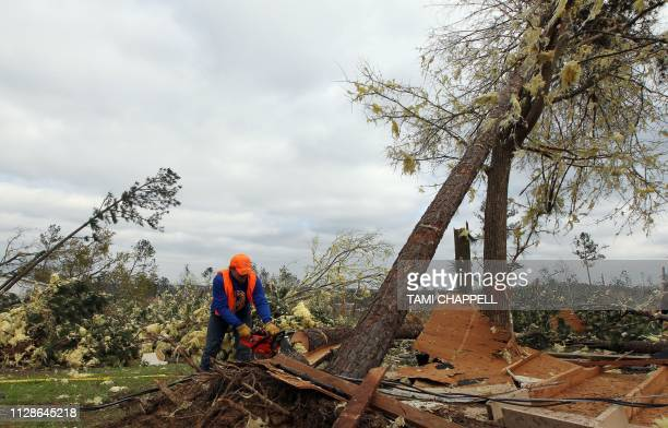 Resident Sean Brown cuts a tree next to what was his home after a tornado struck in Beauregard Alabama on March 4 2019 Rescuers in Alabama resumed...