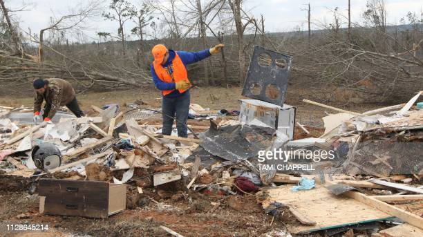 Resident Sean Brown looks for items in the debris with his friend Jonathan Gavins assisting after a tornado struck in Beauregard Alabama on March 4...