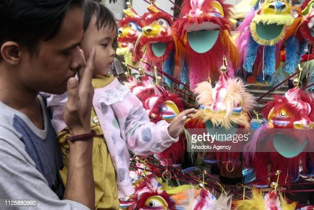 Resident see a miniature of Barongsai during the 'Cap Go Meh' festival that marks the end of the Chinese Lunar New Year celebration in Jakarta...