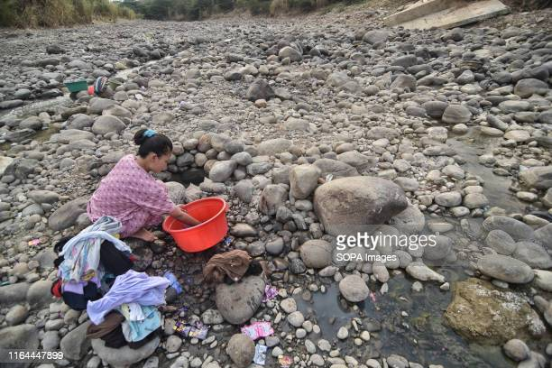 A resident seen washing from a dry Cipamingkis river for domestic use as their wells dry out due to drought in the summer season The Meteorology...