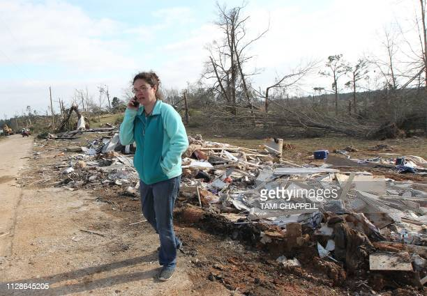 Resident Shannon Kelley talks on the phone as she walks down her street after a tornado struck in Beauregard Alabama on March 4 2019 Kelley told AFP...
