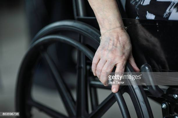 Resident Shelia Fitzpatrick places a hand on her wheelchair as she takes part in an exercise class at Protheroe House in Tottenham on September 5,...