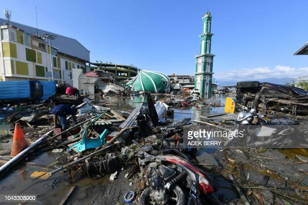 A resident sifts through debris past the rubble of a mosque in Palu Indonesia's Central Sulawesi on September 30 following the September 28...
