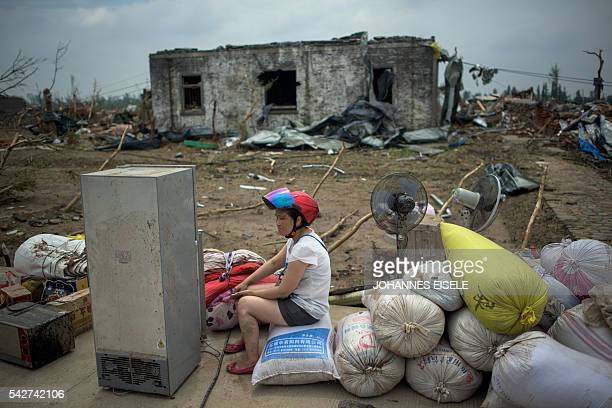 TOPSHOT A resident sits in front of a destroyed house after a tornado in Funing in Yancheng in China's Jiangsu province on June 24 2016 Survivors...