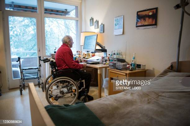 Resident sitting in a wheelchair uses a magnifier for reading in his room in a nursing home in Berlin on January 14 amid the novel coronavirus...