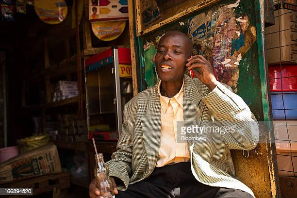 A resident speaks on a mobile phone in Nairobi Kenya on Sunday April 14 2013 In the six years since Kenya's MPesa brought bankingbyphone to Africa...