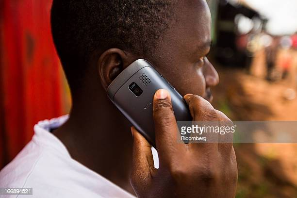 A resident speaks on a Nokia Asha mobile phone on a street in Nairobi Kenya on Sunday April 14 2013 In the six years since Kenya's MPesa brought...
