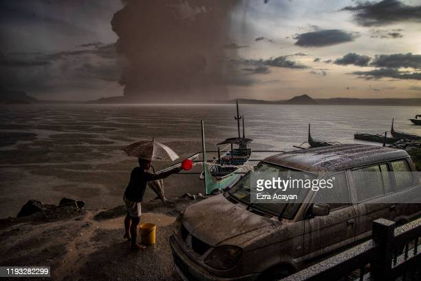 Resident splashes water on a vehicle covered in ash mixed with rainwater as Taal Volcano erupts on January 12, 2020 in Talisay, Batangas province,...