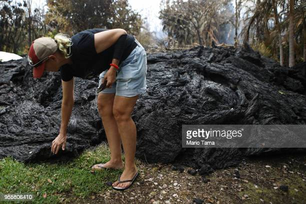 Resident Stacy Welch inspects lava located about 250feet from her home which remains standing in the Leilani Estates neighborhood in the aftermath of...