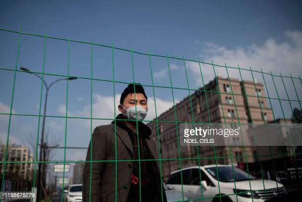 A resident stands beside a barricade along a street in Hangzhou some 175 kilometres southwest of Shanghai on February 5 near the Alibaba headquarters...