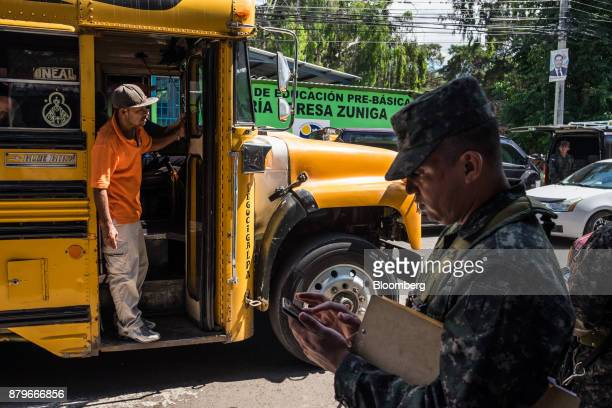 A resident stands in a school bus as soldiers are deployed for security measures ahead of the presidential elections in Tegucigalpa Honduras on...