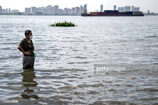 Resident stands in water near to the Jiangtan park that flooded because of heavy rains along the Yangtze river on July 8th, 2020 in Wuhan,...
