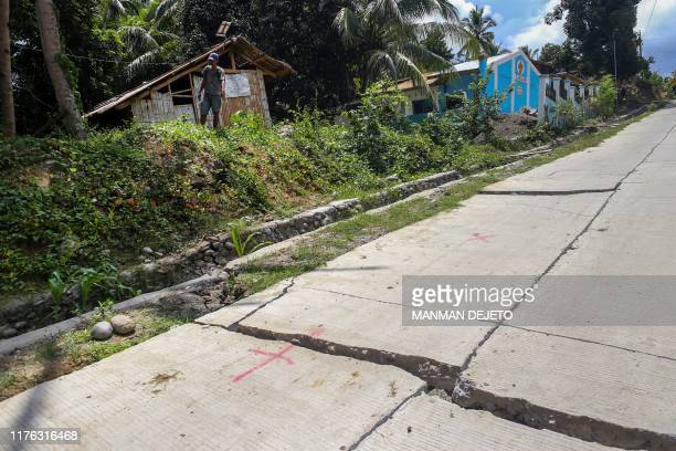 Resident stands near a huge crack in a cemented road caused by a 6.4 magnitude earthquake the night before, in the town of Magsaysay in Davao del Sur...