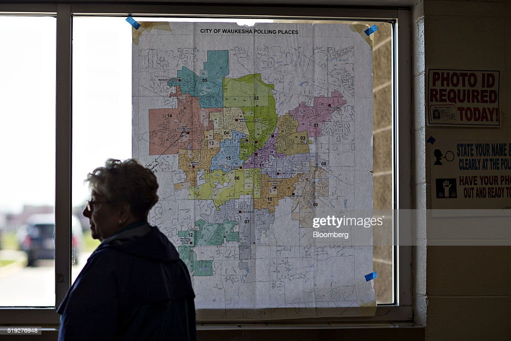 A resident stands near a map of local polling places during the presidential primary vote in Waukesha, Wisconsin, U.S., on Tuesday, April 5, 2016. Wisconsin voters went to the polls Tuesday to decide whether Donald Trump's latest self-inflicted wounds are deep enough to deny him a win in the state's Republican primary, and, in turn, to diminish his hopes of winning the presidential nomination. Photographer: Daniel Acker/Bloomberg via Getty Images