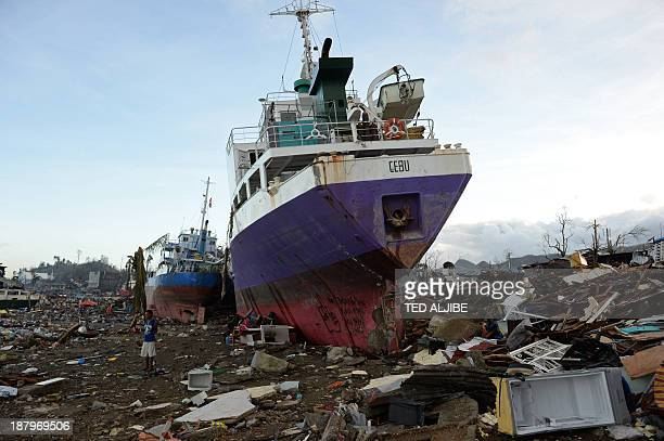 Resident stands next to ships swept ashore at the height of Typhoon Haiyan in Tacloban city, Leyte province, central Philippines on November 14,...