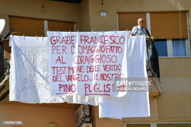 A resident stands on a balcony by a sheet reading Thank you Francis for the hommage you paid to the courageous testimony of the Gospel's truthour...