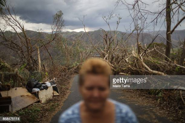 A resident stands outside her house while posing more than two weeks after Hurricane Maria hit the island on October 6 2017 in Morovis Puerto Rico...