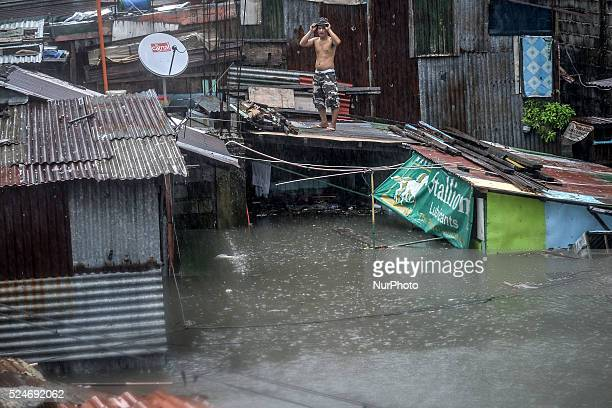 A resident stays on a rooftop to escape rising floodwaters in Quezon city suburban Manila Philippines September 19 2014 Torrential rains spawned by...