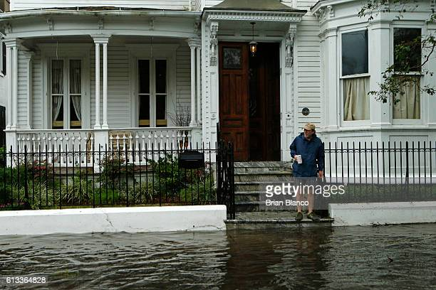 A resident stops short of the flooded sidewalk as he makes his way to the edge of the steps in front of a friend's home on Broad St in the wake of...