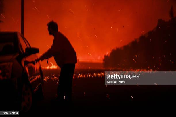 A resident struggles to open his car door to evacuate as flames get closer to homes north of on December 5 2017 in Ventura California