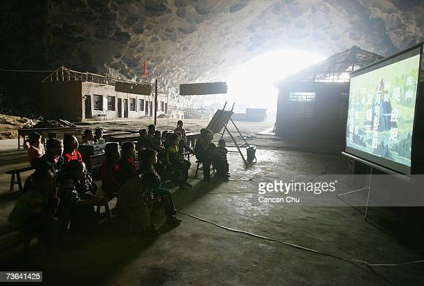 Resident students watch cartoons on a donated projector in the enormous cave that serves as home and school near a remote Miao village March 15 2007...