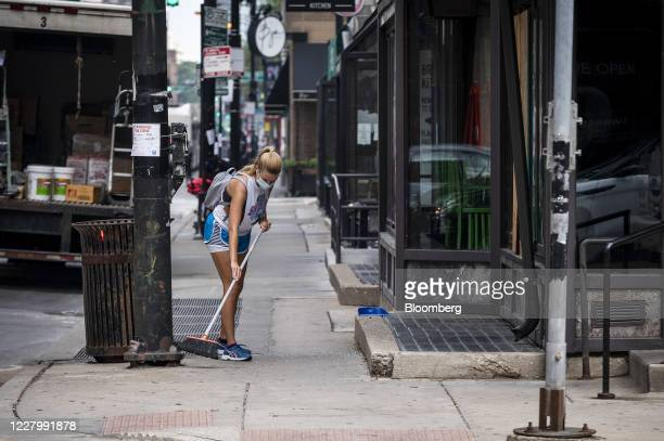 Resident sweeps up glass from the street following looting in Chicago, Illinois, U.S., on Monday, Aug. 10, 2020. Chicago police arrested more than...