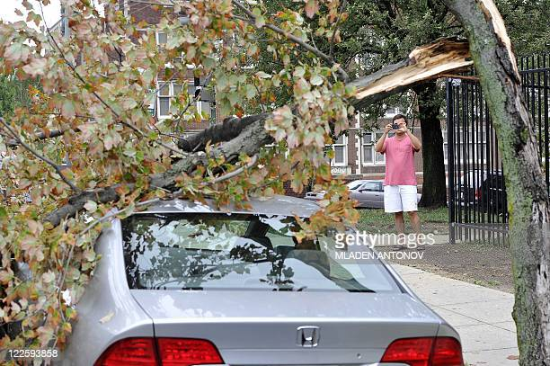 A resident take photos with his mobile phone of a downed tree that lies over a car on a street in the Northwest neighborhood of Washington DC August...