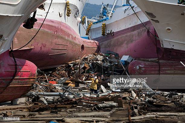 A resident takes pictures at the place where four ships were wrecked by the recent tsunami in Kesennuma city Miyagi prefecture on April 14 2011...