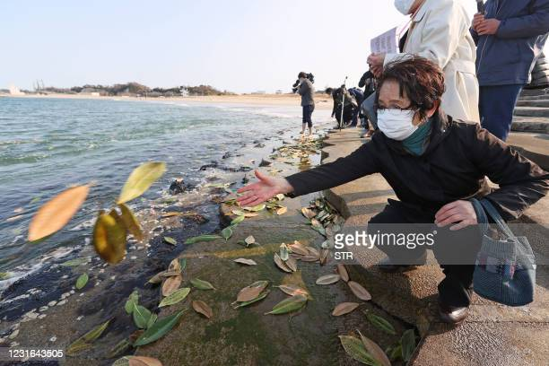 Resident throws leaves, bearing messages to loved ones, to the sea in Soma, Fukushima prefecture on March 11 the 10th anniversary of the...