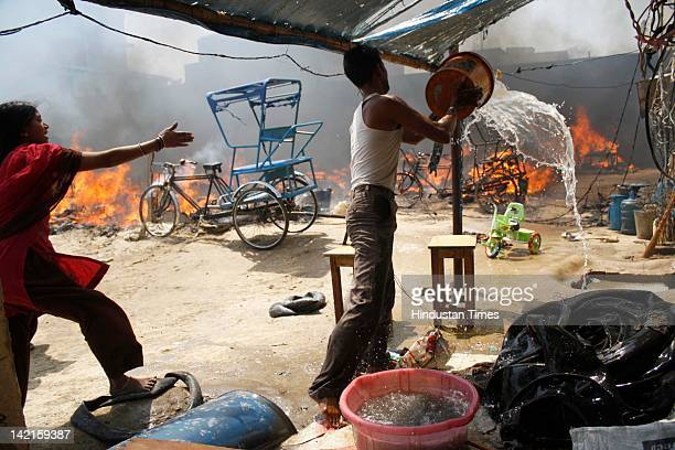 Resident trying to quench the fire at Navada village, Sector-62 on March 31, 2012 in Noida, India. Reportedly, two children lost their lives in the...