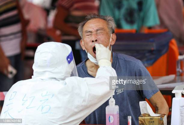 Resident undergos a nucleic acid test for the Covid-19 coronavirus in Xiamen, in China's eastern Fujian province on September 14, 2021. - China OUT /...