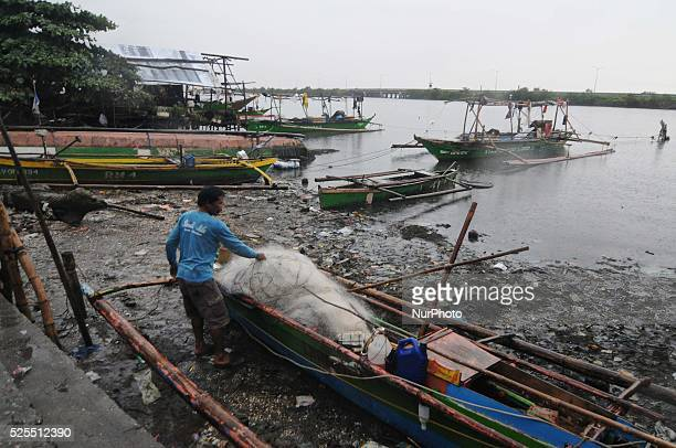 A resident unloads nets off a fishing boat docked along a fishing village in Bacoor south of Manila Philippines November 8 2013 Thousands of people...