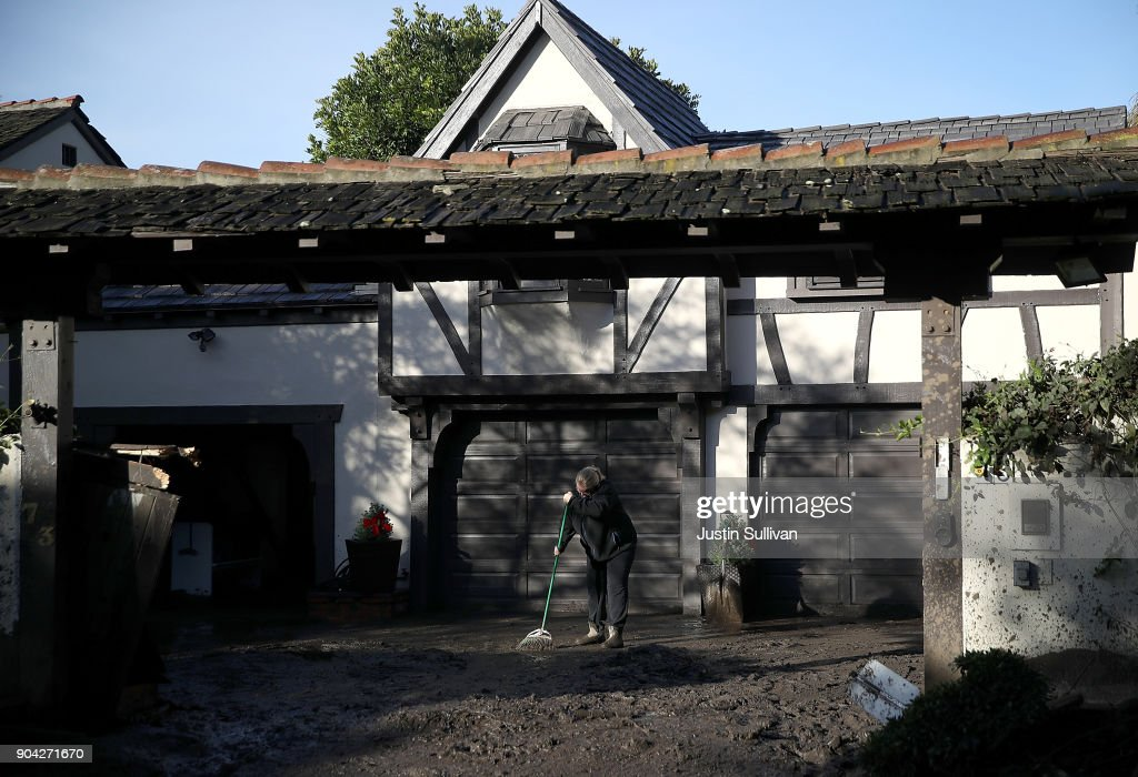 A resident uses a broom to clean mud from in front of her home following a mudslide on January 12, 2018 in Montecito, California. 17 people have died and hundreds of homes have been destroyed or damaged after massive mudslides crashed through Montecito, California early Tuesday morning.