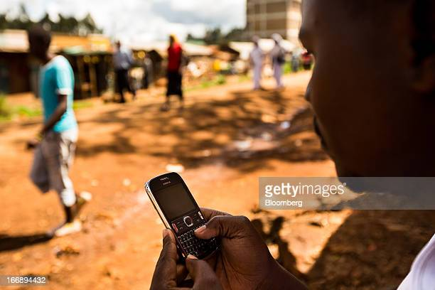 A resident uses a Nokia Asha mobile phone on a street in Nairobi Kenya on Sunday April 14 2013 In the six years since Kenya's MPesa brought...