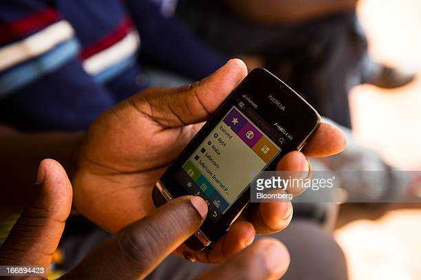 A resident uses a Nokia Oyj mobile phone in Nairobi Kenya on Sunday April 14 2013 In the six years since Kenya's MPesa brought bankingbyphone to...
